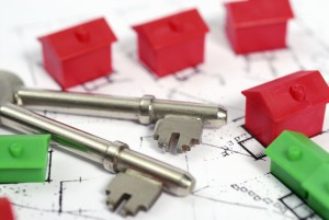 House buying. House keys on a housing plan with green and red model houses.